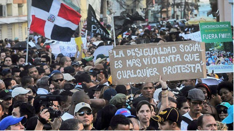 Dominicans protest against higher taxes and school privatization amid government corruption. Police killed one student at the protest where a sign reads: Social inequality is more violent than any protest."